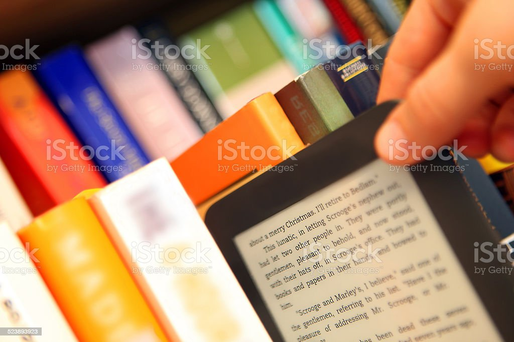 Hand Choosing an E-Book vs. Paper Books from a Bookshelf stock photo