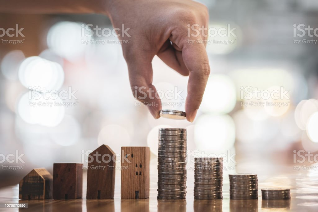 Hand choosing row of coin money on wood table and mini wood house, selective focus, Planning to buy property. Choose what's the best. A symbol for construction ,ecology, loan concepts stock photo