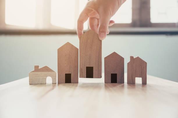 scelta a mano modello di casa in legno, mutuo e investimento immobiliare - locatario foto e immagini stock