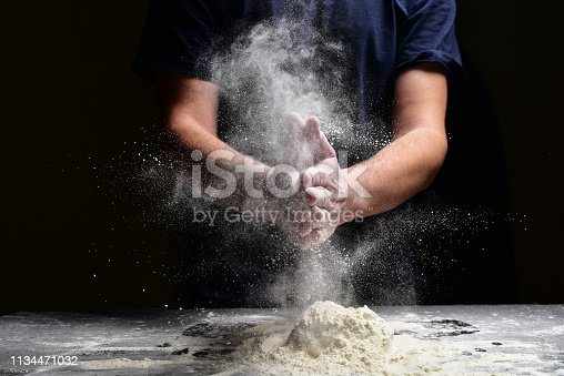 Hand clap of chef with splash flour on black background