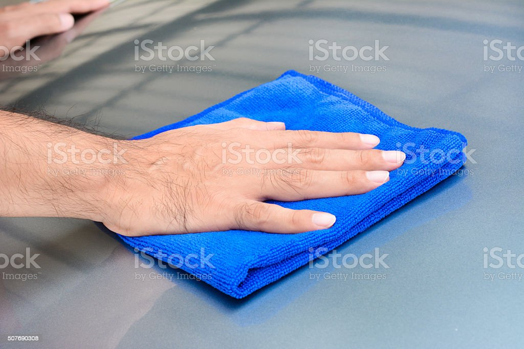 Hand cleaning car bonnet with microfiber cloth stock photo