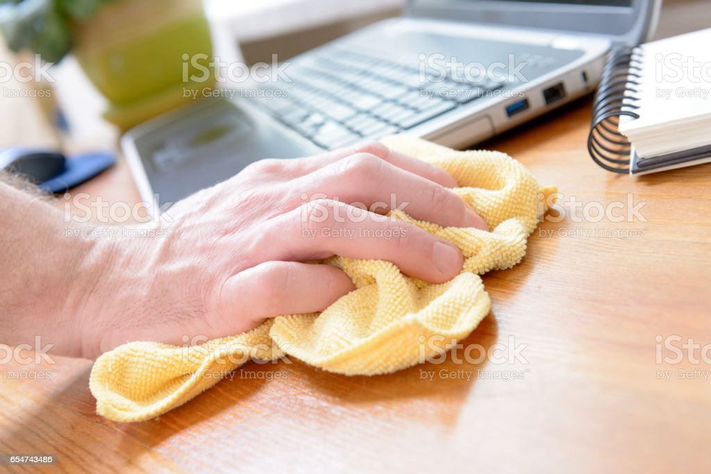 Hand cleaning desk at home stock photo