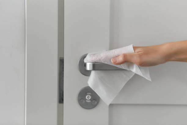 hand cleaning door handle with antiseptic wet wipe stock photo