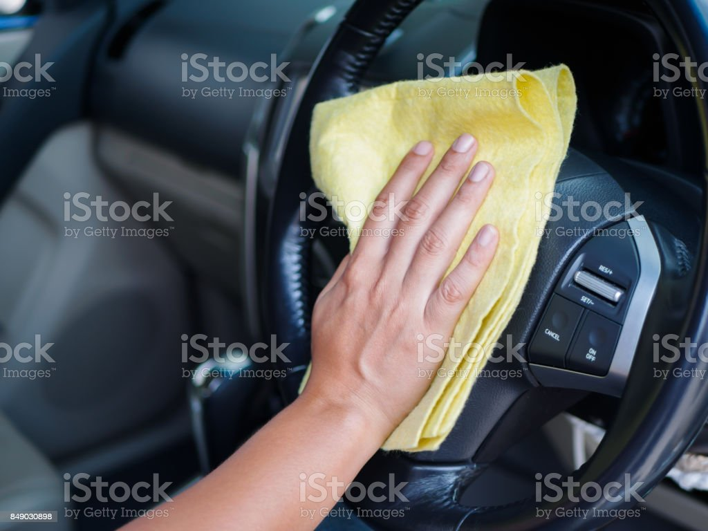 Hand cleaning interior car steering wheel with microfiber cloth. stock photo