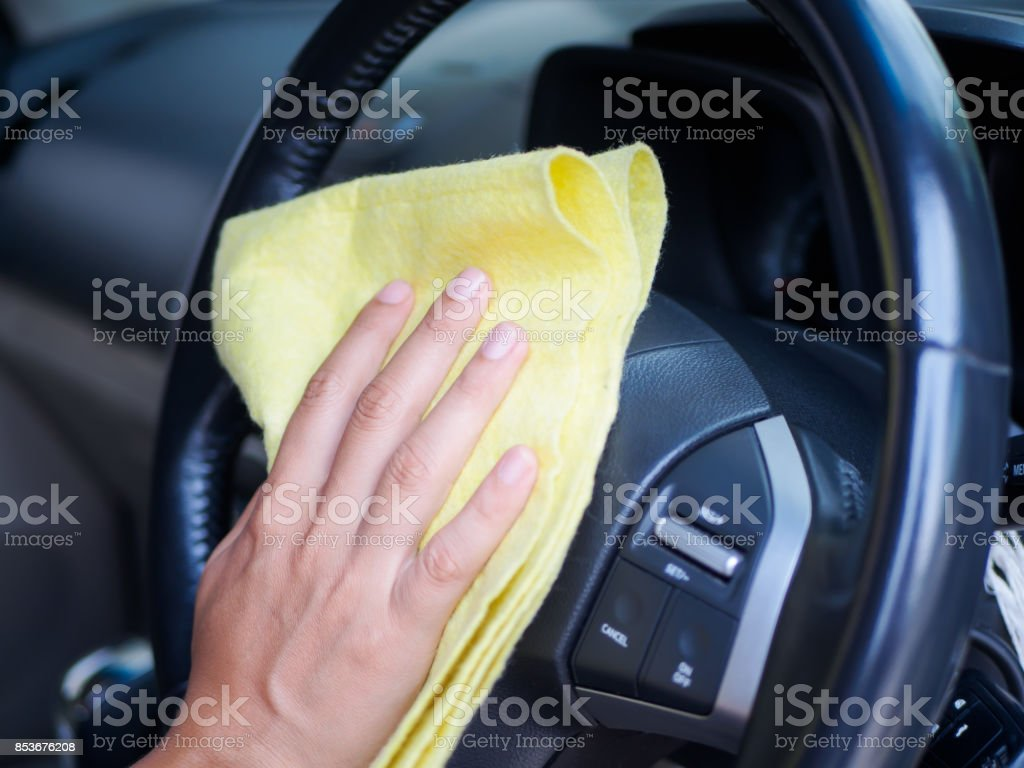 Hand cleaning interior car steering wheel with microfiber cloth stock photo