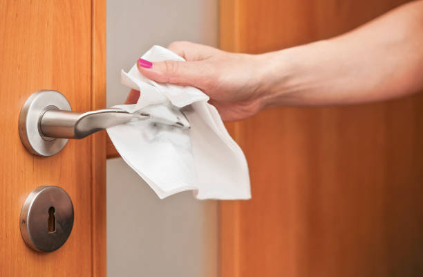 Hand cleaning metal door handle with paper tissue towel, closeup detail - coronavirus covid-19 spread prevention stock photo