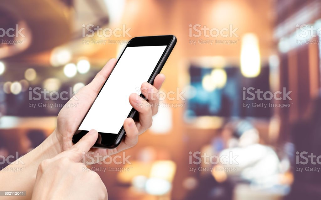 Hand click mobile phone with blur chef at restaurant background bokeh light,White screen mock up template for adding your design or your text stock photo