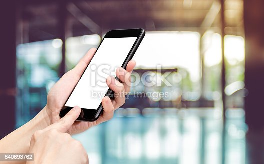 istock Hand click mobile phone with blur office corridor hall way background bokeh light,White screen mock up template for adding your design or your text 840693762