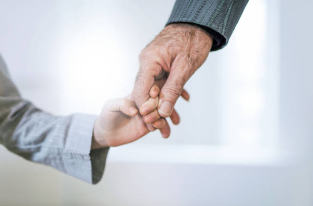 Hand close-up of grandfather and granddaughter holding hands. Hand close-up of grandfather and granddaughter holding hands. granddaughter stock pictures, royalty-free photos & images