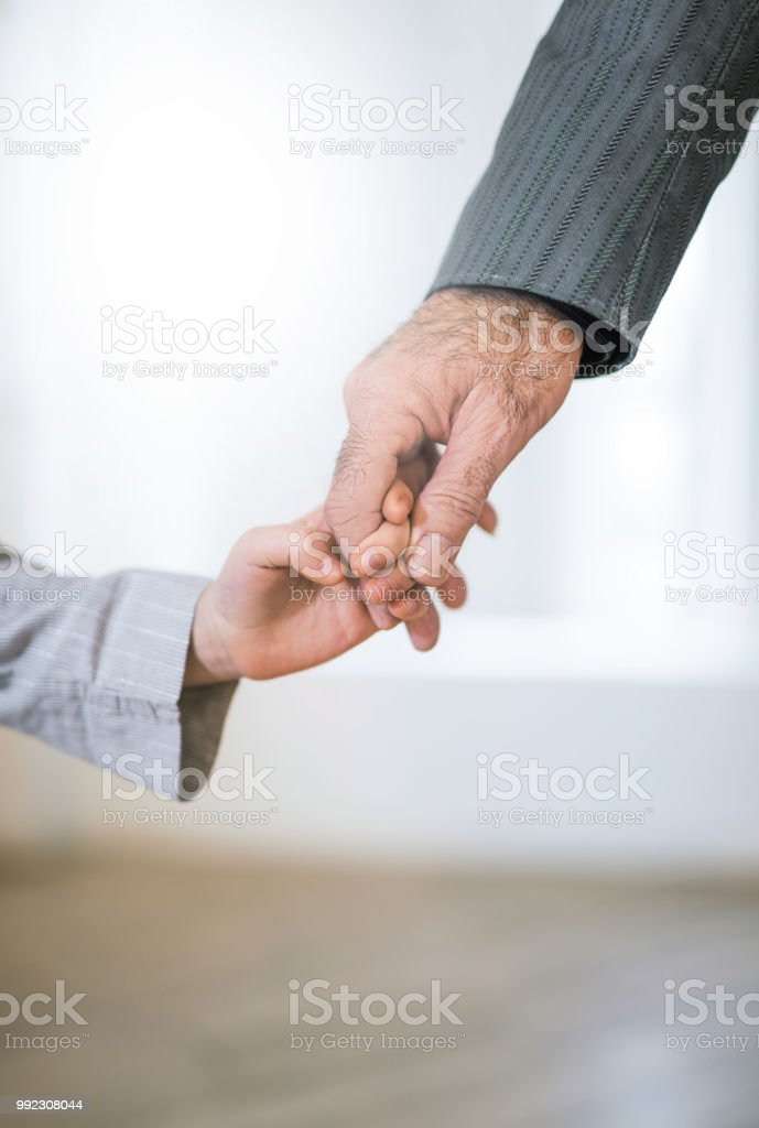Hand close-up of grandfather and granddaughter holding hands. stock photo