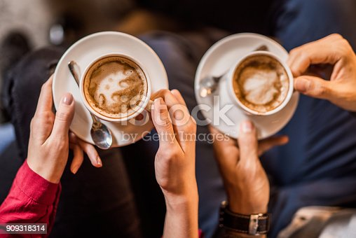 Hand close-up of young couple holding coffee cups.