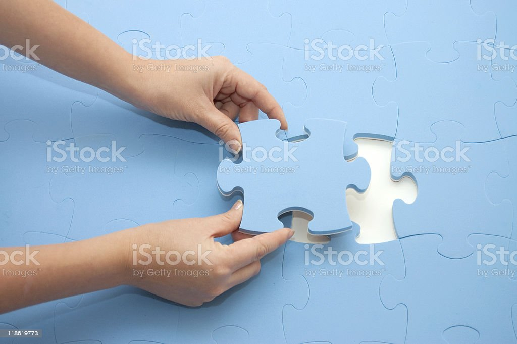 Hand collecting a part of  puzzle stock photo
