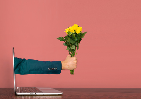 Hand coming out of a laptop with yellow roses in hand. Valentine's day Covid Concept.