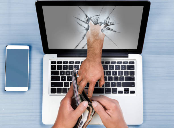 Hand coming out of computer stealing money stock photo