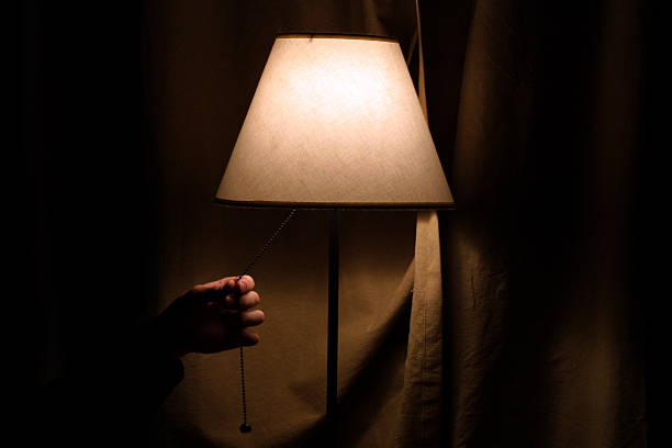 Hand coming to turn off a cream bedside lamp