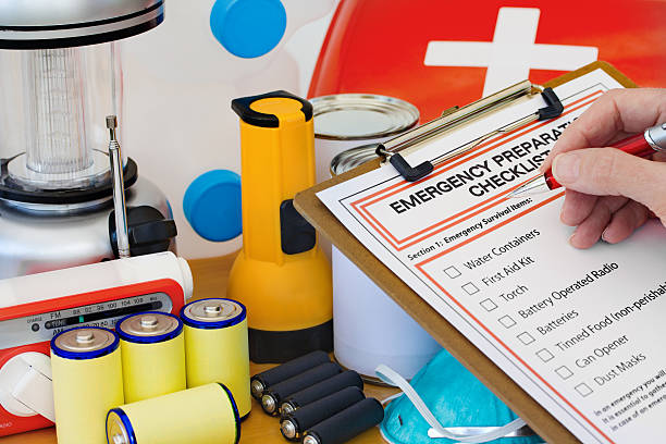 Hand completing Emergency Preparation List by Equipment Ready for disaster - checking off the items on the emergency  preparedness form accidents and disasters stock pictures, royalty-free photos & images