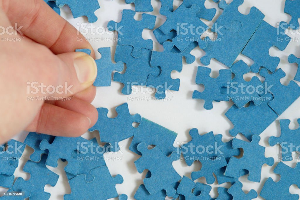hand connecting blue jigsaw puzzle pieces together on white