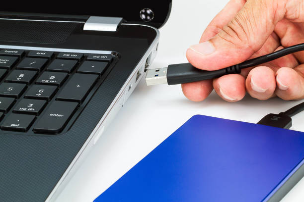 Hand connecting external hard drive usb cable to laptop on white desk Hand connecting external hard drive usb cable to laptop on white desk external hard disk drive stock pictures, royalty-free photos & images