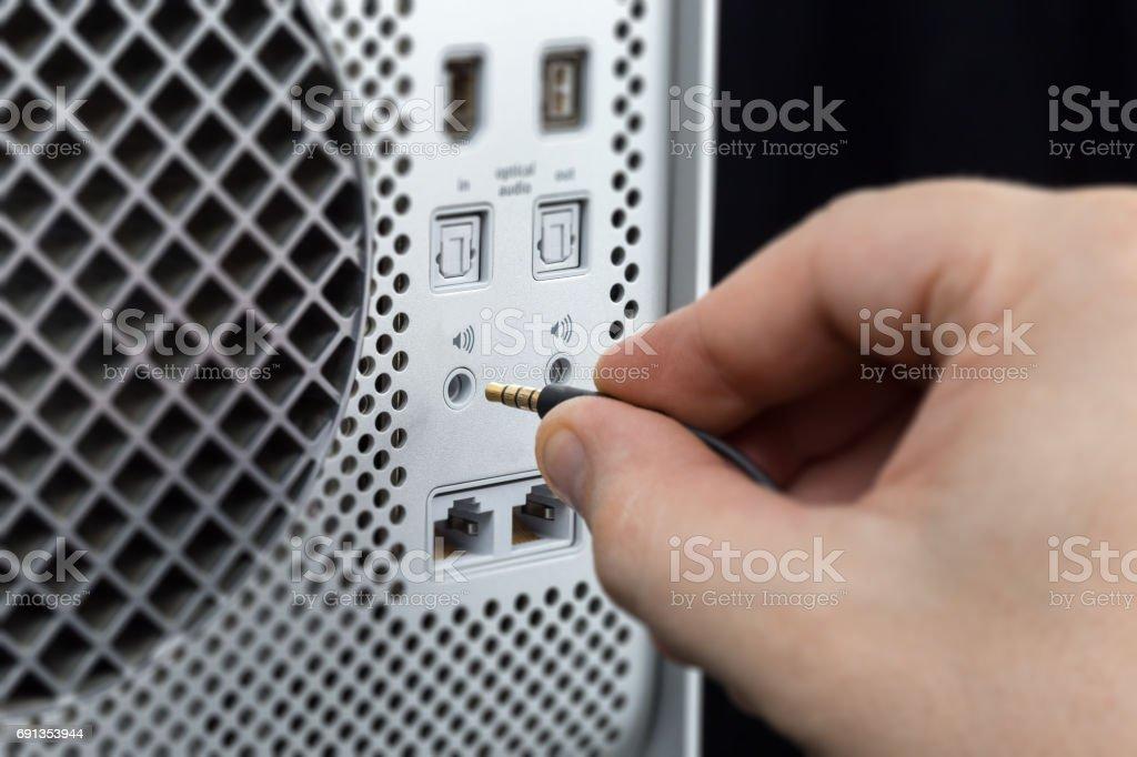 Hand connecting minijack to the computer stock photo