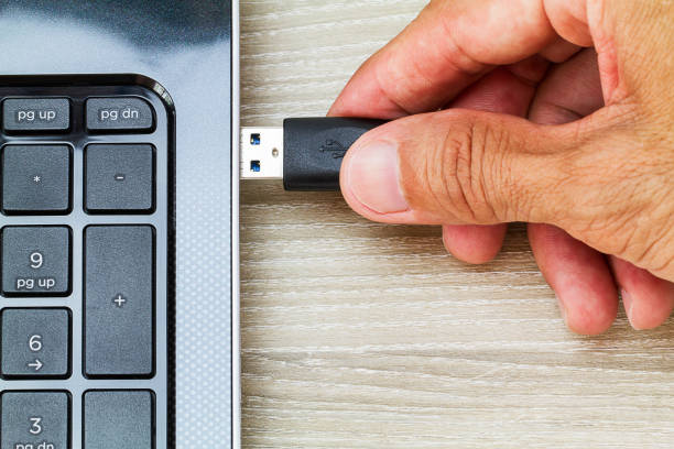 Hand connecting USB cable to laptop computer on wooden desk Hand connecting USB cable to laptop computer on wooden desk external hard disk drive stock pictures, royalty-free photos & images