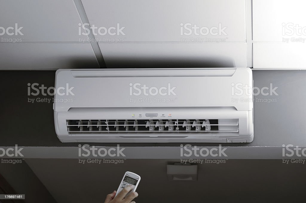 Hand controlling an air conditioner stock photo