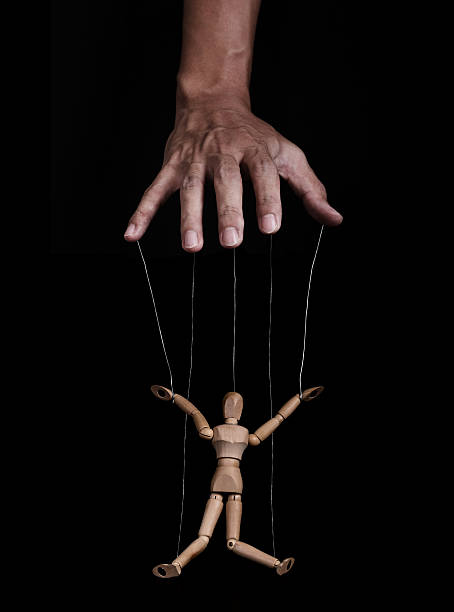 Hand controlling wooden puppet, low key images, on black background Hand controlling wooden puppet figure, low key images, on black background puppet stock pictures, royalty-free photos & images