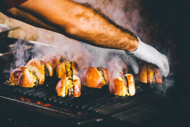 Hand cooking burgers on a hot flaming grill Detail of chef hands with gloves cooking cheeseburgers on a hot flaming grill smoke and flames bbq for an outdoor festival food festival stock pictures, royalty-free photos & images