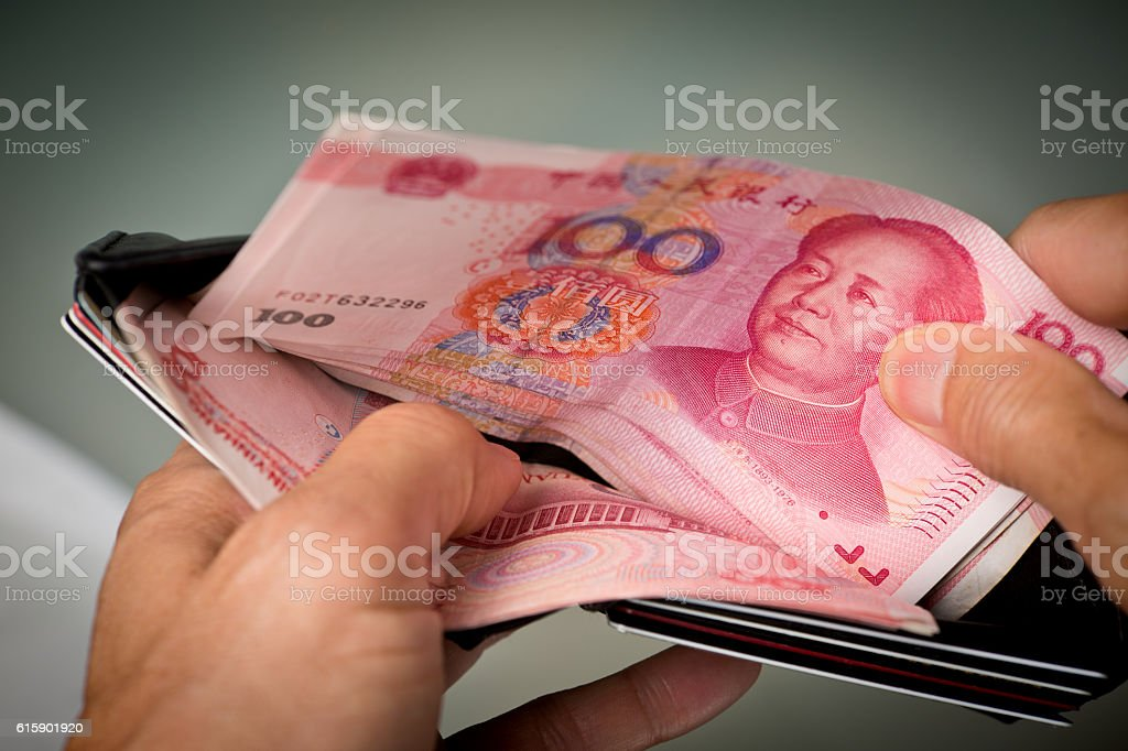 Hand Counting Chinese Yuan Currency in Wallet stock photo