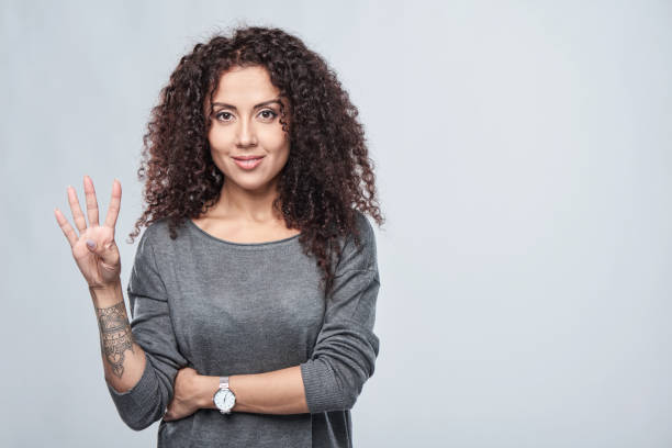 Hand counting - four fingers. Hand counting - four fingers. Smiling woman showing four fingers number 4 stock pictures, royalty-free photos & images