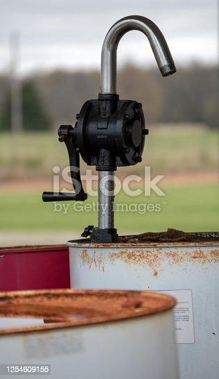 A defocused foreground and background draws the eye to the hand crank pump on the rusty barrel of old oil.