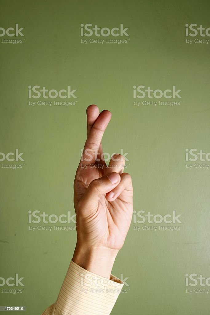 Hand crossing fingers stock photo