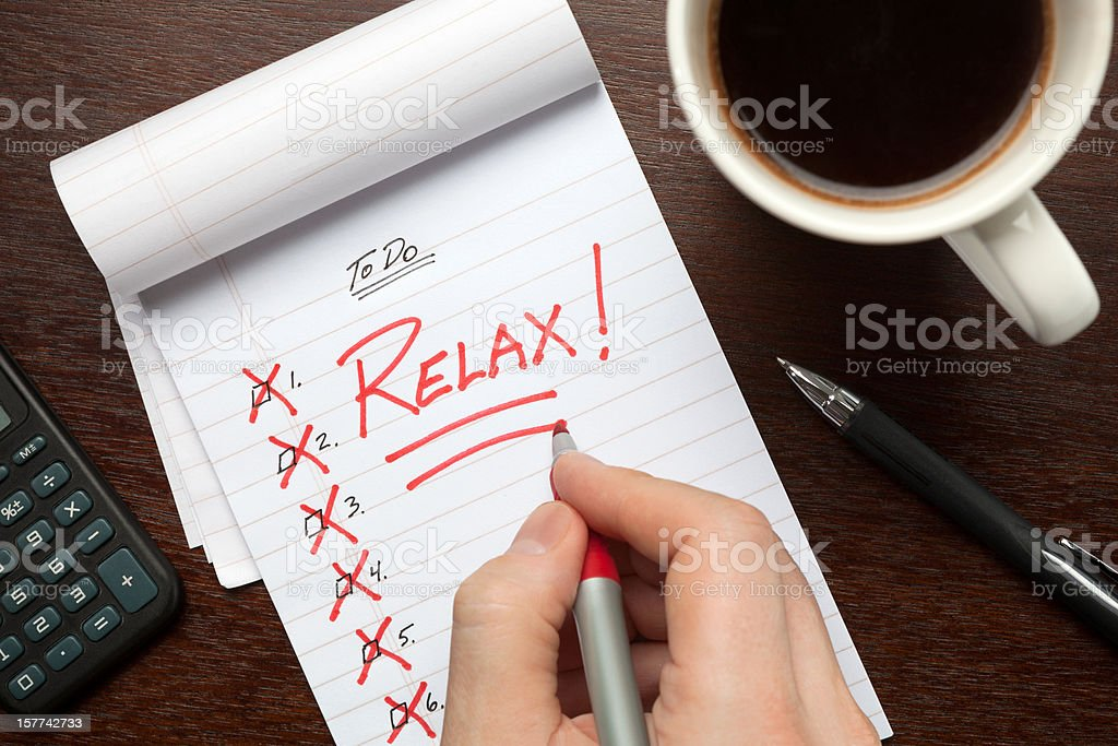 A to do list crossed off with a hand writing \'relax\' on the notepad.