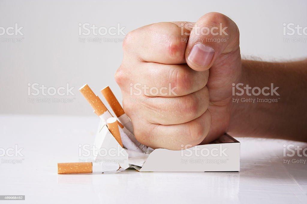 Hand crushing cigarettes stock photo