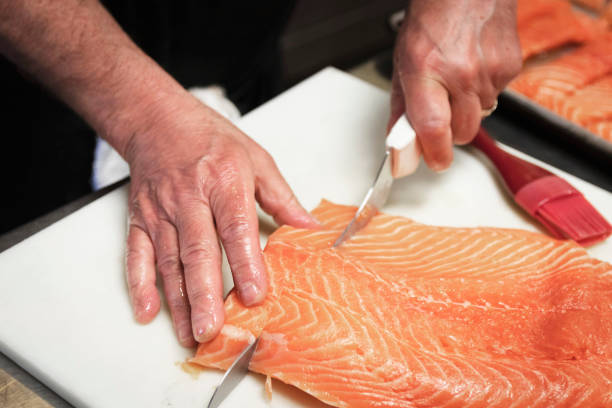 Hand cutting steaks of salmon stock photo
