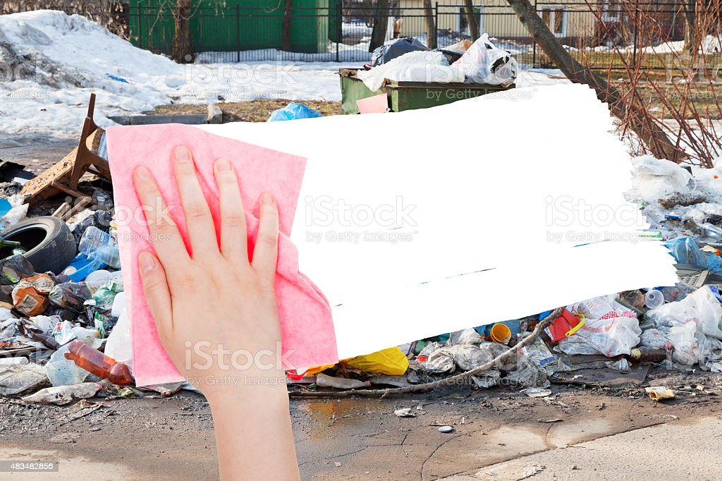 hand deletes urban dumpster by pink rag stock photo
