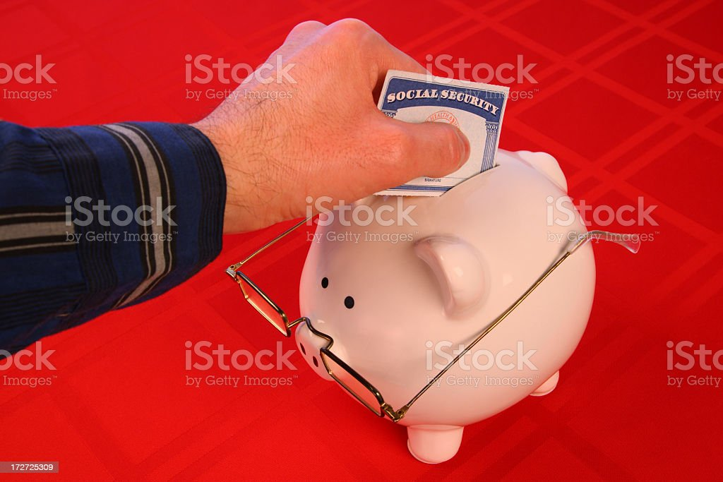 Hand Depositing Social-Security Card into Piggy Bank with Glasses royalty-free stock photo