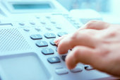 istock A hand dialing on a landline phone 174685963