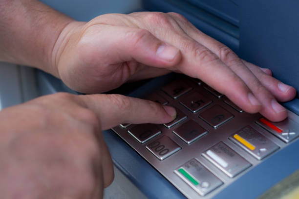 hand dials the PIN code at an ATM stock photo