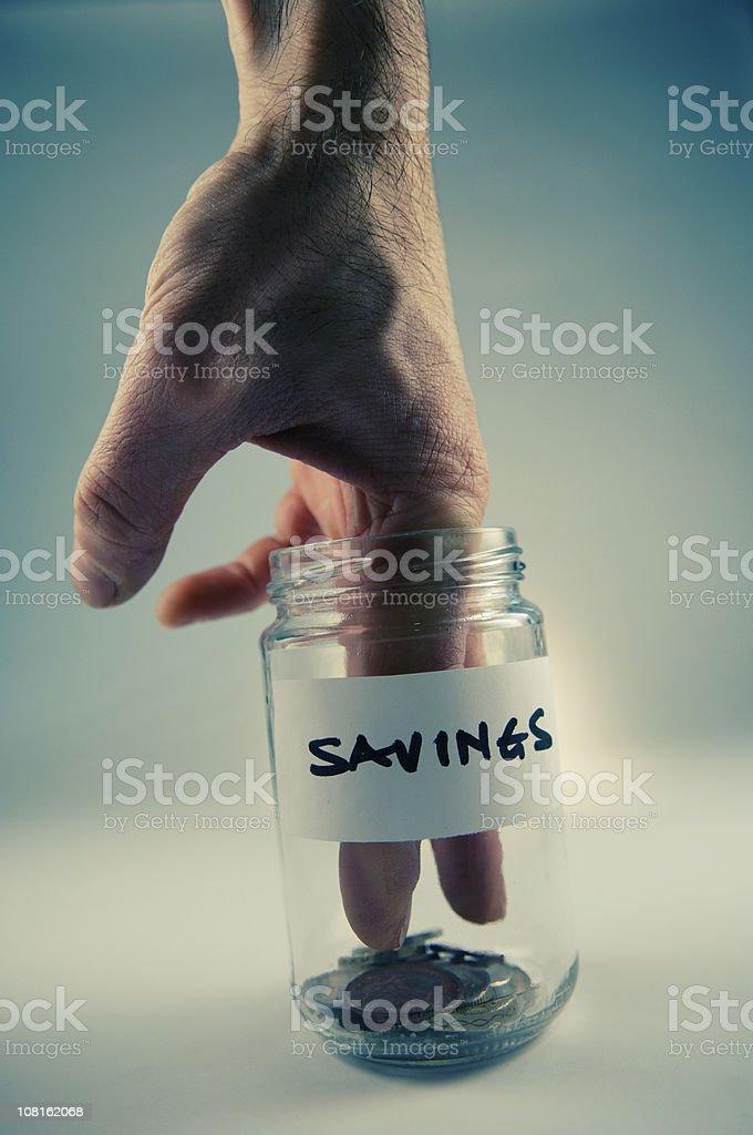 Hand Dipping Into Savings Jar royalty-free stock photo