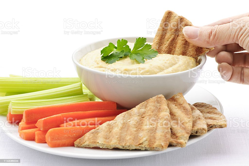 Hand dipping pita in hummus royalty-free stock photo