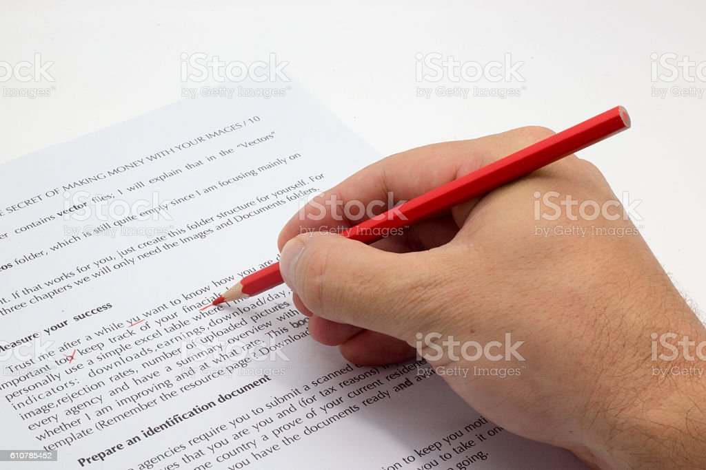 Hand doing proofreading on a faulty text with red pen stock photo