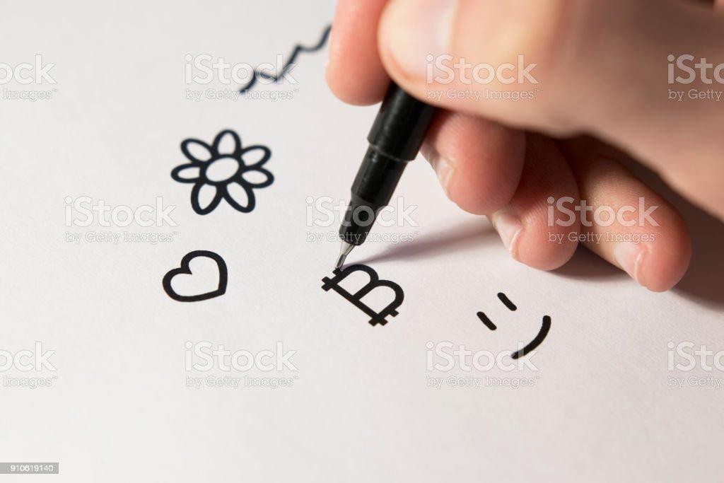 Hand Drawing a Bitcoin Symbol stock photo