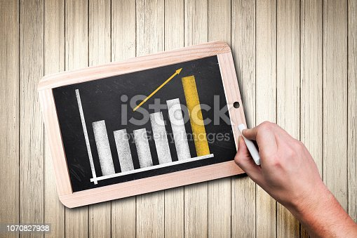 hand drawing a chart on a chalkboard, flat lay from top on wooden table