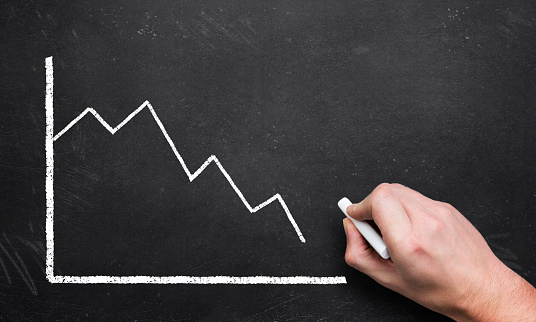 istock hand drawing a decreasing chart on a blackboard 1094073486