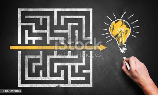hand drawing a shortcut through a maze to an idea on a chalkboard