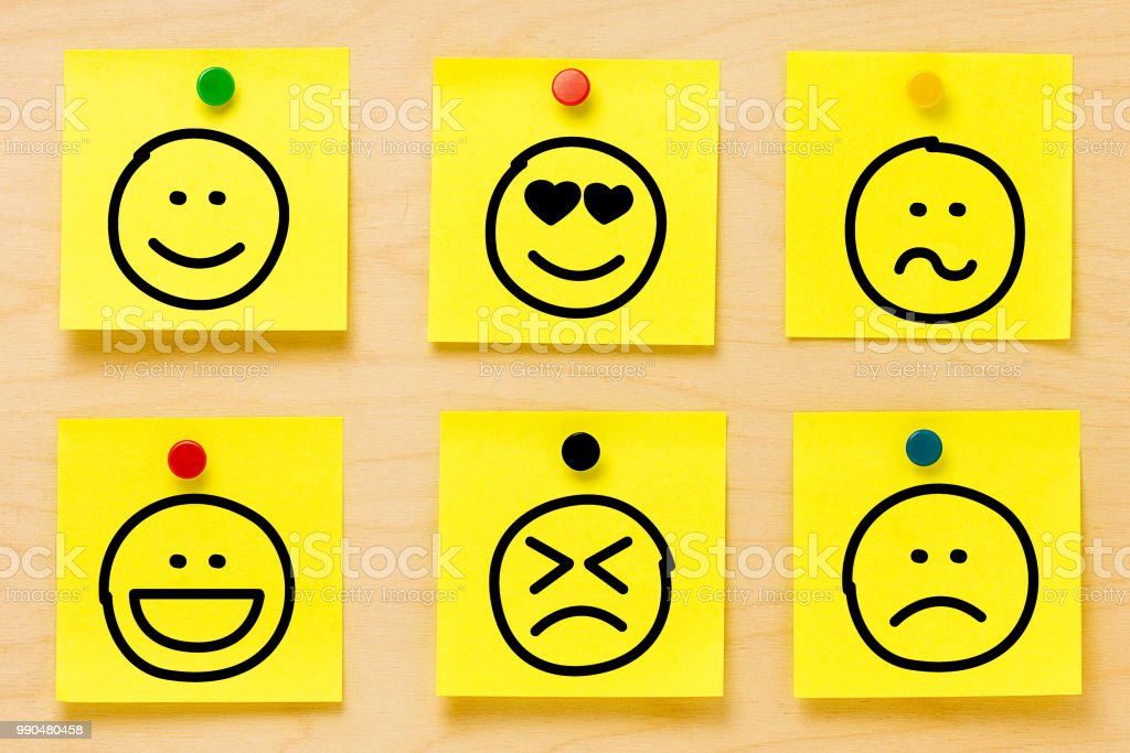 Hand drawing emoticons on six yellow postit notes affixed by colored pins on a wooden board stock photo