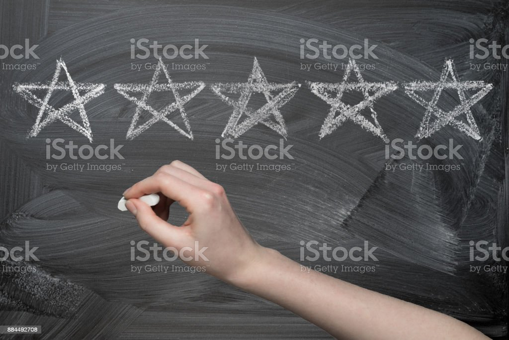 Hand drawing five stars rating on chalkboard stock photo