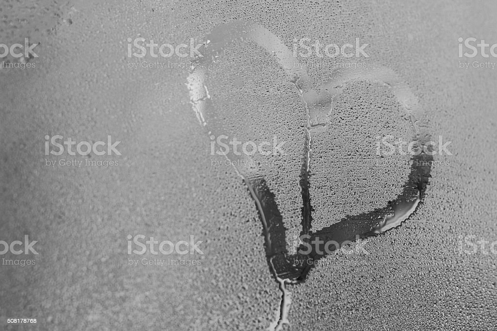 Hand drawing heart on the wet window glass stock photo