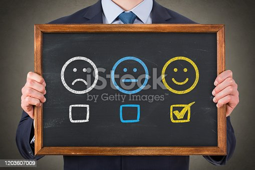 517629622 istock photo Hand Drawing Unhappy and Happy on Chalkboard Background 1203607009