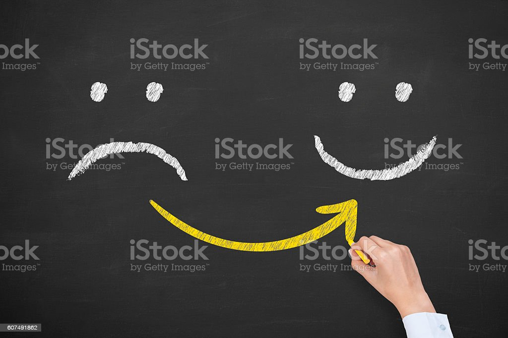 Hand drawing unhappy and happy smileys on blackboard background stock photo